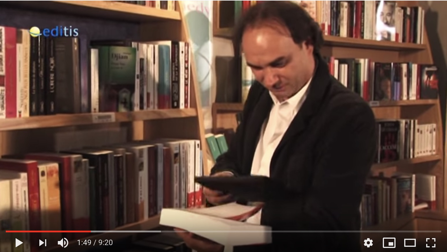 Screencapture from an Editis video showing a man with a book in a bookstore  scanning with his e-reader.