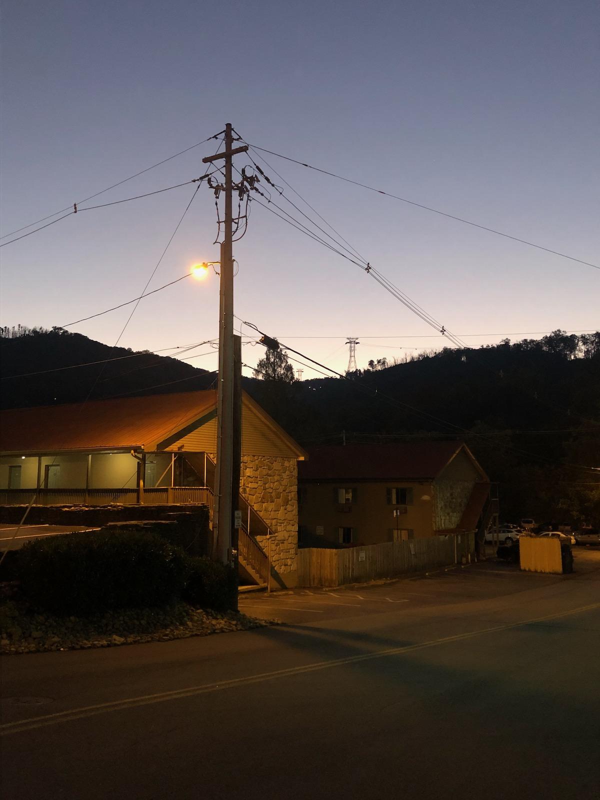 Empty, street, dimly lit houses, electrical pole.