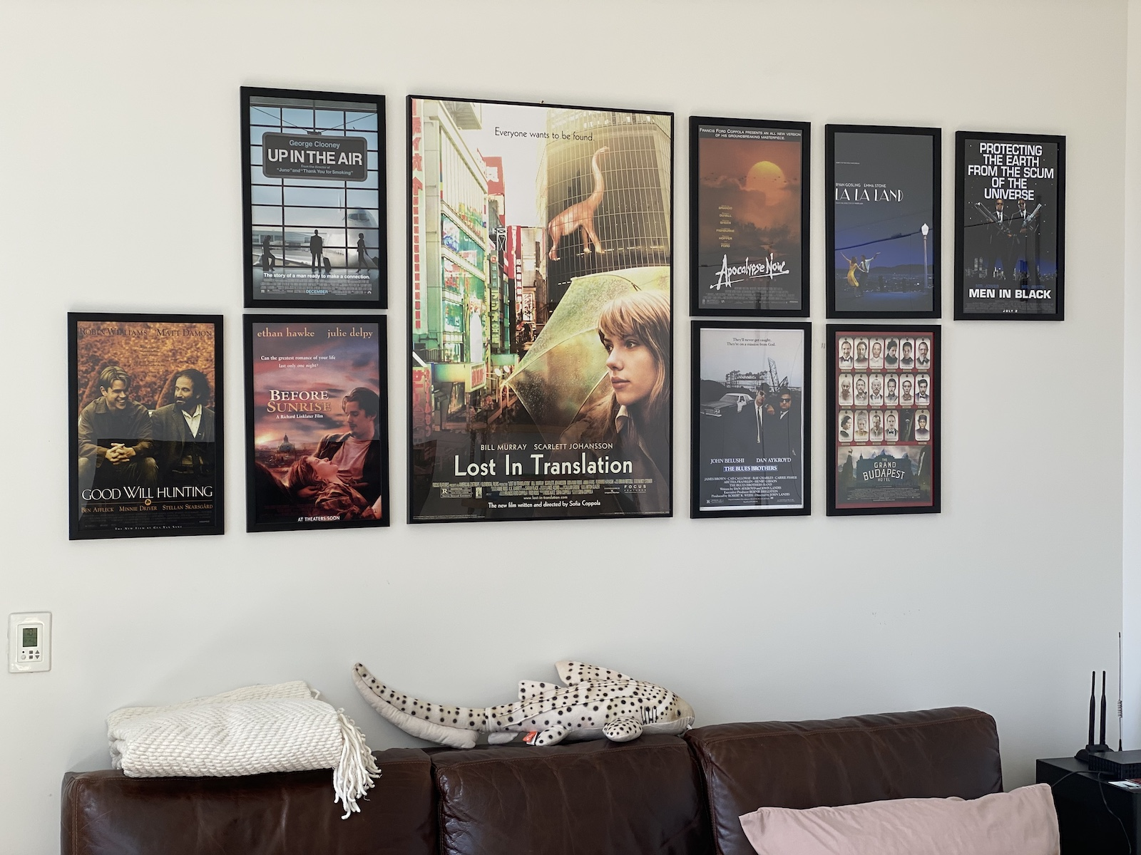 The wall behind my couch with 9 movie posters: Good Will Hunting, Before Sunrise, Up in the Air, Lost in Translation, Apocalypse Now, The Blues Brothers, Grand Budapest Hotel, La La Land, and Men in Black.