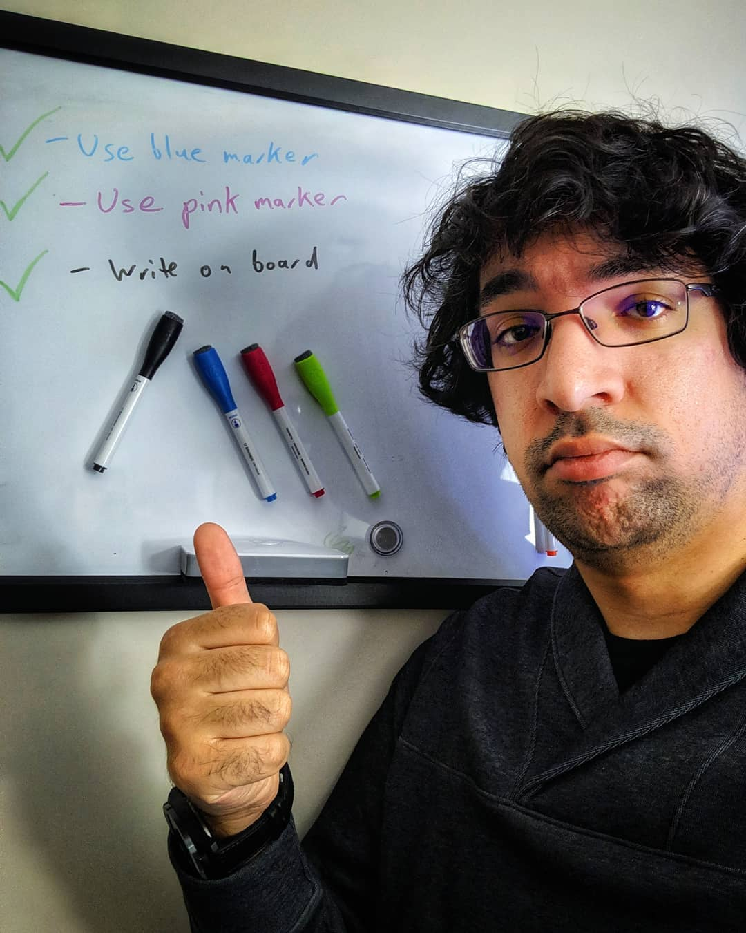 Photo of me pointing to a whiteboard with three completed tasks: Use blue marker, Use pink marker, Write on board.