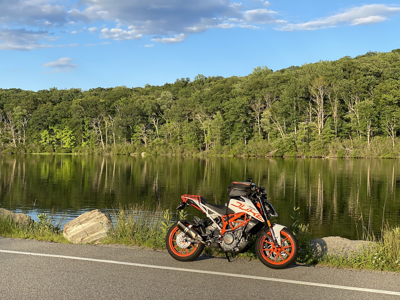 My Duke 390 sitting on the side of the road with a background of a pond and some woods reflecting on it.