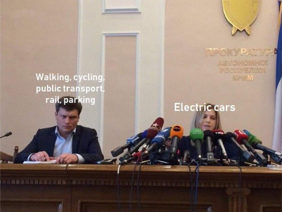 A meme of a press conference where the person on the left has no microphone and looks disappointed, and the person on the right has 20 press microphones in front of her. The person on the left with no attention has the caption Walking, cycling, public transport, rail and parking. The person on the right with all the attention has a caption reading Electric cars