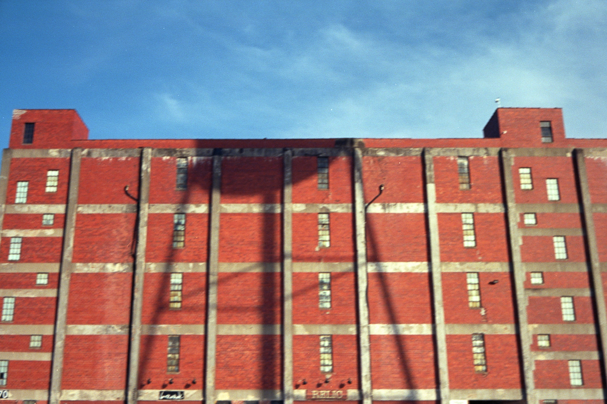 Blurry: shadow of a water tower on an orange industrial building.